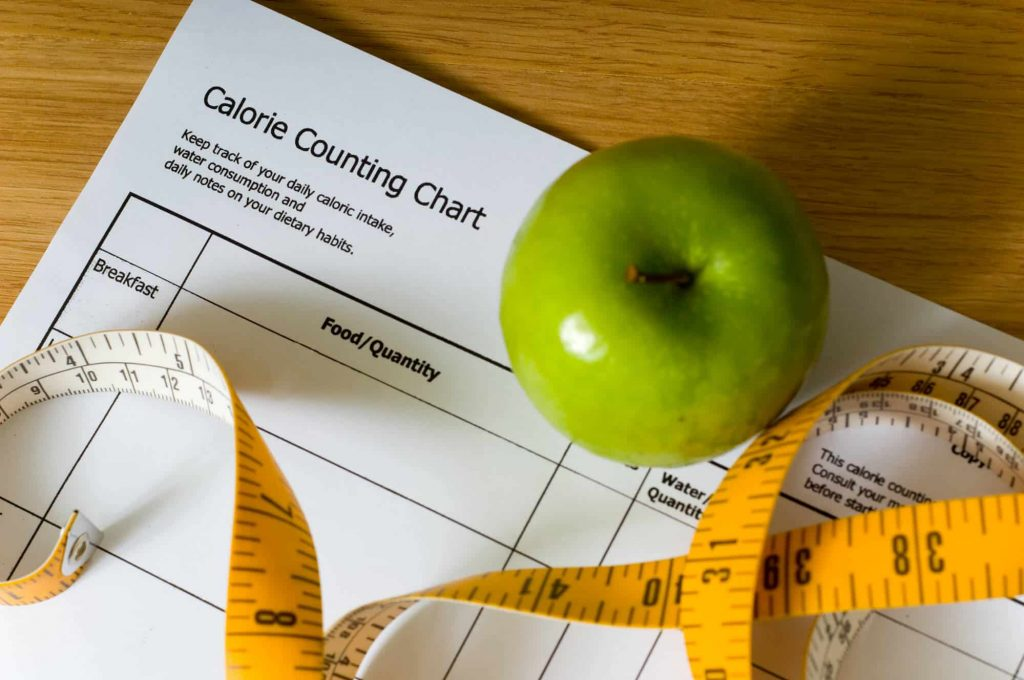 Calorie count chart, green apple and tape measure, items for a diet