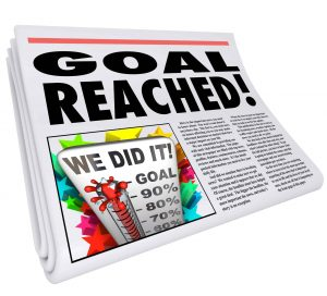 A newspaper headline Goal Reached and article with picture of thermometer with level at 100% and words We Did It