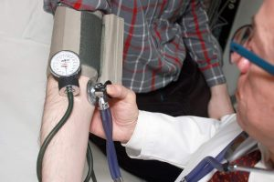 a doctor taking the blood pressure in case of side effects to amino energy