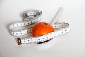 an orange wrapped around a tape measure