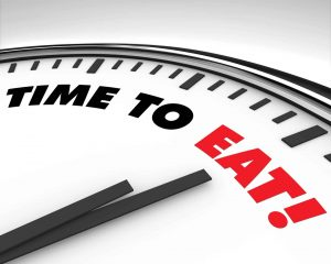 White clock with words Time to Eat on its face
