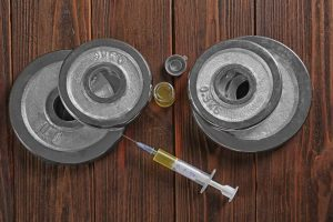 Weight disks and syringe on wooden background